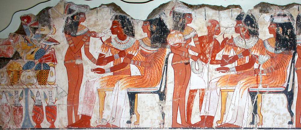 A feast for Nebamun. An entire wall of the tomb-chapel showed a feast in honour of Nebamun. Naked serving girls and servants wait on his friends and relatives. Married guests sit in pairs on fine chars, while the young women turn and talk to each other. This erotic scene of relaxation and wealth is something for Nebamun to enjoy for all eternity. The richly dressed guests are entertained by dancers and musicians, who sit on the ground playing and clapping. Thebes, Egypt,  18th Dynasty, around 1350 BC