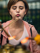 03 SEPTEMBER 2015 - BANGKOK, THAILAND: A woman lights candles and incense at the Four Faced Brahma statue at Erawan Shine. Repairs to Erawan Shrine were completed Thursday, Sept 3 after the shrine was bombed on August 17. Twenty people were killed in the bombing and more than 100 injured. The statue of the Four Faced Brahma in the shrine was damaged by shrapnel and a building at the shrine was damaged by debris.      PHOTO BY JACK KURTZ