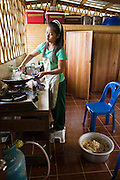 18 FEBRUARY 2008 -- BONG TI, KANCHANABURI, THAILAND: A girls makes dinner for other refugee children at the Bamboo School in Bong Ti, Thailand, about 40 miles from the provincial capital of Kanchanaburi. Sixty three children, most members of the Karen hilltribe, a persecuted ethnic minority in Burma, live at the school under the care of Catherine Riley-Bryan, whom the locals call MomoCat (Momo is the Karen hilltribe word for mother). She provides housing, food and medical care for the kids and helps them get enrolled in nearby Thai public schools. Her compound is about a half mile from the Thai-Burma border. She also helps nearby Karen refugee villages by digging water wells for them and providing medical care.  Photo by Jack Kurtz