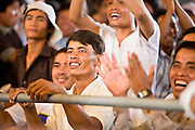 02 JULY 2006 - PHNOM PENH, CAMBODIA: Fans cheer for their fighter during a traditional Khmer boxing match in Phnom Penh, Cambodia. Khmer boxing is the same sport as Muay Thai (traditional Thai kick boxing) but because off animosity between Thailand and Cambodia it is called Khmer Boxing in Cambodia. The Cambodians claim to have invented the sport, which is also practiced in Laos and Burma. Photo by Jack Kurtz
