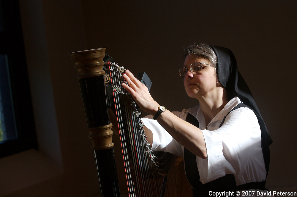 Sister Kathleen O'Neill tunes her harp in the chapel of Our Lady of the Mississippi Abbey, a monastery of Trappist nuns.  O'Neill practices on a daily basis, and plays at many of the daily services.  The community of 22 Roman Catholic women follow Jesus Christ through a life of prayer, silence, simplicity and ordinary work.  Their home is a beautiful monastery which sits high on a bluff, overlooking the Mississippi River.