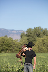 cowboy walking through a meadow with a saddle