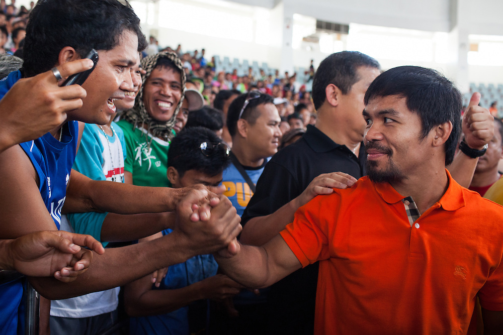 Manny Pacquiao greets a man in the crowd inside the Tacloban City Astrodome Convention Center.<br /> <br /> Manny Pacquaio visits victims of Typhoon Yolanda in Tacloban City.  Leyte, Philippines  December 2, 2013