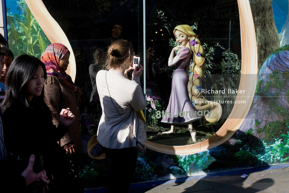 Disney character Rapunzel from their film Tangled stands looking at passers-by, exemplifying feminine beauty.