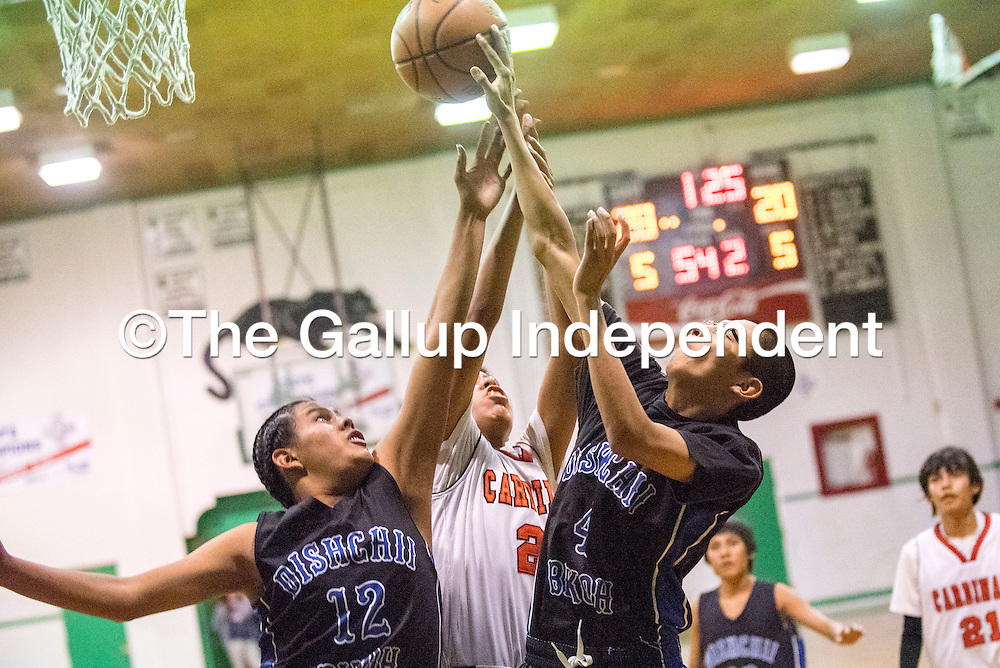 122214  Adron Gardner/Independent<br /> <br /> Cibecue Wildcats and a St. Michael Cardinal battle for a rebound at Gallup Catholic School Monday.