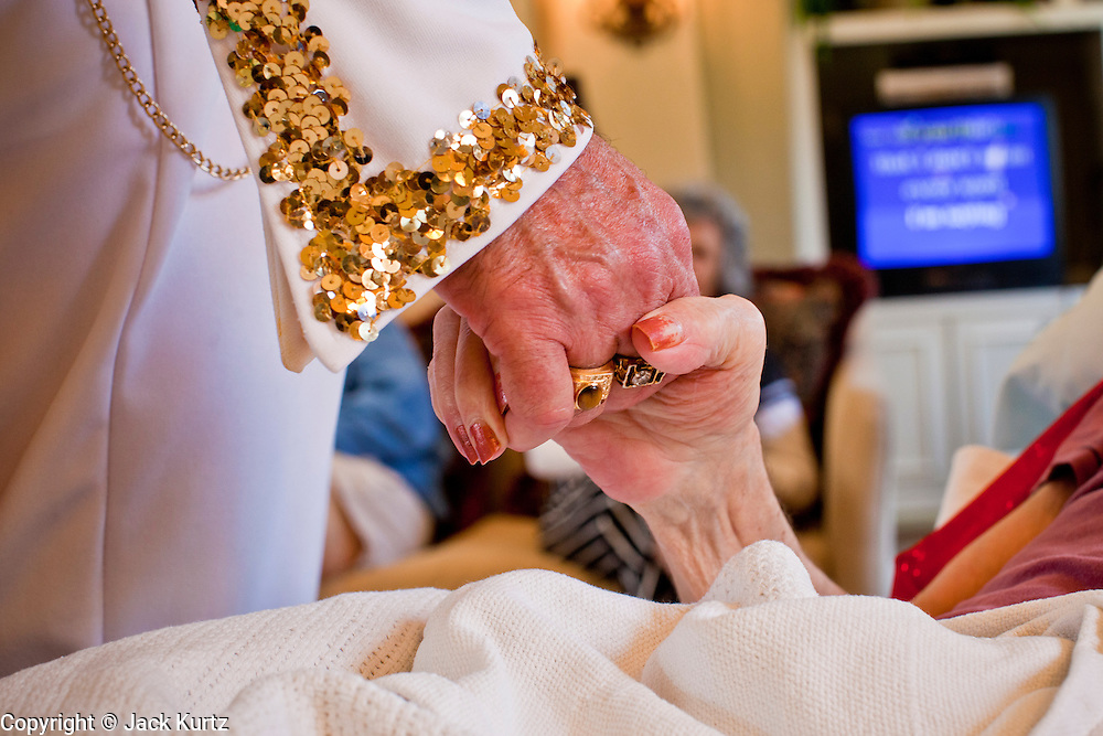 Aug. 2 - PHOENIX, AZ:  DONALD TRAPANI, dressed as Elvis Presley, holds the hand of WANDA DINKINS while he sings to her at the Stratford, an Alzheimer's care facility in Phoenix. Trapani, 68, was diagnosed with lung cancer in August 2009 and entered the care of Hospice of the Valley, the largest hospice organization in Phoenix, shortly after that. His doctor said he would be dead by the end of February 2010. Trapani is in still in the care of Hospice of the Valley, but his condition has improved. He now entertains other hospice patients singing the songs of Elvis Presley. He tries to hold one concert each week, his health permitting, at different hospice units in the Phoenix area.     Photo by Jack Kurtz