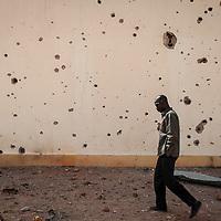 26/01/2013. Konna, Mali. Visite de la presse à Konna, la ville occupée par les islamistes située le plus au sud au Mali. Elle est à 70 kilomètres au nord de Sevaré, point stratégique pour son aéroport.  Un homme passe devant le mur du bâtiment principal du port de pêche de Konna criblé de balles. ©Sylvain Cherkaoui