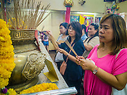 "24 FEBRUARY 2013 - BANGKOK, THAILAND: People pray in the ""coffin temple"" of the Ruamkatanyu Foundation next to Wat Hua Lamphong. The Ruamkatanyu Foundation provides coffins for Bangkok's indigent and emergency medical services for accident victims in Bangkok. Wat Hua Lamphong is a Royal Buddhist temple, third class, in the Bang Rak District of Bangkok, Thailand. It is located on Rama IV Road, approximately 1 km from the city's main Hua Lamphong railway station. An entrance to Sam Yan Station on the Bangkok metro (subway) is located outside the main entrance to the temple compound on Rama IV. Wat Hua Lamphong was renovated in 1996 to mark the 50th anniversary of the ascension to the throne of King Bhumibol Adulyadej (Rama IX) in 1996. The royal seal of what became known as the Kanchanapisek, or Golden Jubilee, year, showing two elephants flanking a multi-tiered umbrella, are featured in the temple's remodeling.     PHOTO BY JACK KURTZ"