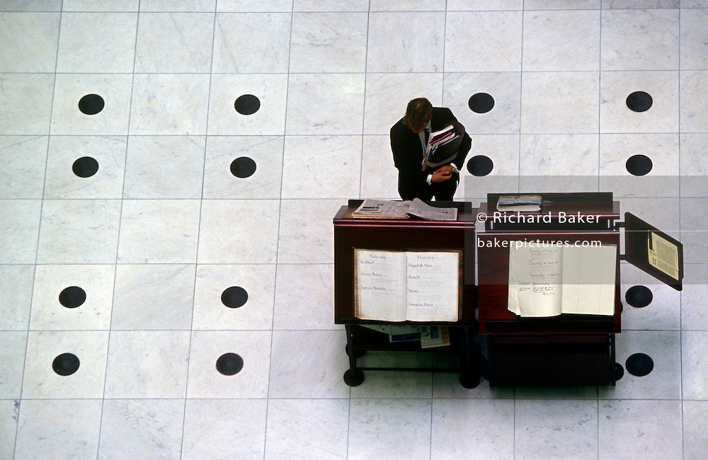 An insurance underwriter or broker stands on the floor at Lloyds of London's Richard Rogers headquarters building. He reads pages from what is known as the Loss Book, a centuries-old tradition. Since the time of Edward Lloyd's Coffee House in the seventeenth century, the Loss Book has been the focal point for gathering intelligence and keeping a record of the commercial ships lost to the mighty oceans. Today, a feature of visits to Lloyd's is a look at the famous Loss Book and an example of its counterpart from 100 years earlier. The Lloyds market began around 1688 and is today the world's leading insurance market providing specialist insurance services to businesses in over 200 countries and territories.
