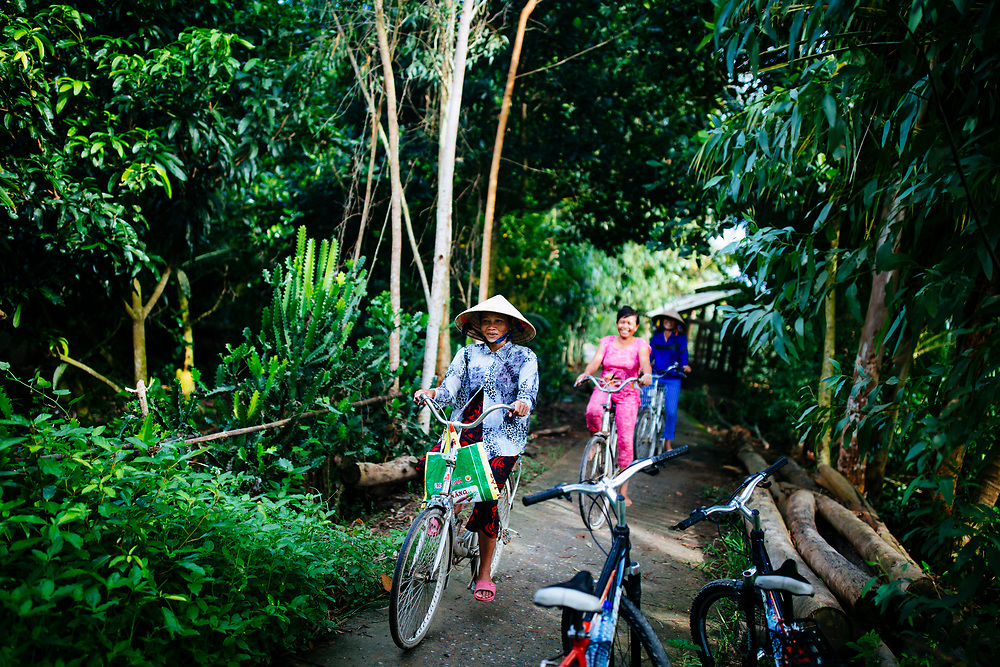 Women ride bicycles through a small village backroad in the Mekong Delta in southern Vietnam.
