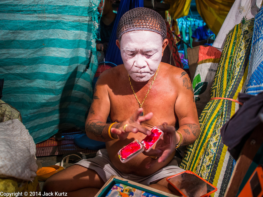 23 SEPTEMBER 2014 - BANGKOK, THAILAND:  A performer at the Chinese opera puts on his makeup on the first day of the Vegetarian Festival at the Chit Sia Ma Chinese shrine in Bangkok. The Vegetarian Festival is celebrated throughout Thailand. It is the Thai version of the The Nine Emperor Gods Festival, a nine-day Taoist celebration beginning on the eve of 9th lunar month of the Chinese calendar. During a period of nine days, those who are participating in the festival dress all in white and abstain from eating meat, poultry, seafood, and dairy products. Vendors and proprietors of restaurants indicate that vegetarian food is for sale by putting a yellow flag out with Thai characters for meatless written on it in red.    PHOTO BY JACK KURTZ