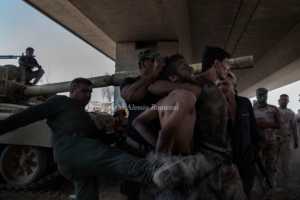 IRAQ, Mosul: An alleged ISIS fighter is mistreated by Iraqi armi soldiers right after being captured on the frontline in the old city of Mosul. Alessio Romenzi