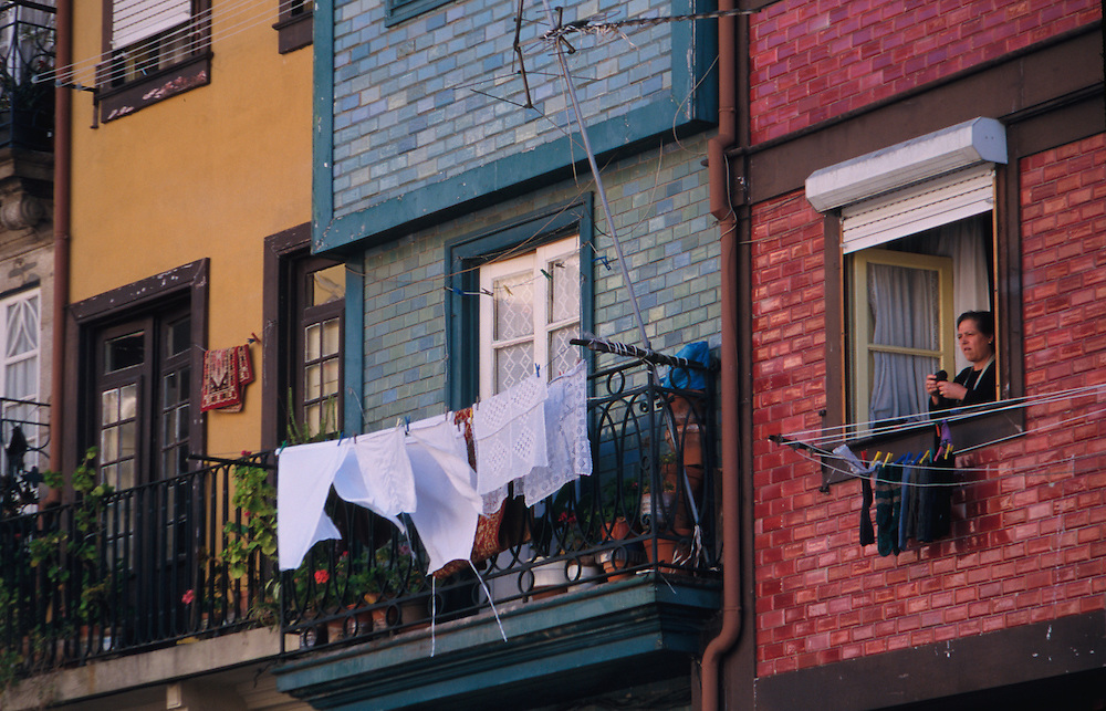 Europe, Portugal, Oporto (also known as Porto) woman at window near laundry line with colorful brick houses