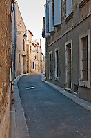Deserted, narrow winding street in the historic city of Arles, southern France.
