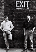 Two friends stand in a back alley behind the cinema on Parkway, Camden, London, UK, 1986.