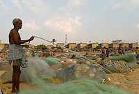 Fisherman tending to his nets. Santhome Beach and adjoining Marina Beach in Chennai, India were hit hard by the 2004 Tsunami. Fishermen and their families were the main victims living in their lightweight huts on the long and flat beaches of the area. All structures within 300 metres of the sea have now been banned and any left standing after the Tsunami were demolished. The fishermen and their families have now been relocated to government blocks of flats which has become a Santhome slum for fishermen and their families.
