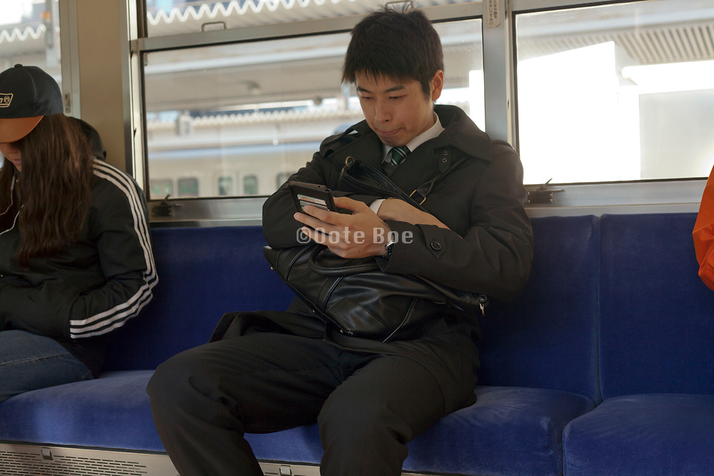 businessman working on his smart phone while commuting Japan