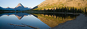 """Sinopah Mountain (8271 feet or 2521 meters) reflects in Pray Lake at sunrise, in Glacier National Park, Montana, USA. Since 1932, Canada and USA have shared Waterton-Glacier International Peace Park, which UNESCO declared a World Heritage Site (1995) containing two Biosphere Reserves (1976). Rocks in the park are primarily sedimentary layers deposited in shallow seas over 1.6 billion to 800 million years ago. During the tectonic formation of the Rocky Mountains 170 million years ago, the Lewis Overthrust displaced these old rocks over newer Cretaceous age rocks. Glaciers carved spectacular U-shaped valleys and pyramidal peaks as recently as the Last Glacial Maximum (the last """"Ice Age"""" 25,000 to 13,000 years ago). Of the 150 glaciers existing in the mid 1800s, only 25 active glaciers remain in the park as of 2010, and all may disappear by 2020, say climate scientists. (Panorama stitched from 4 overlapping images.)"""