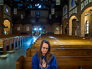 "04 APRIL 2020 - DES MOINES, IOWA: A woman prays herself in St. Anthony Catholic Church in Des Moines. The Des Moines Diocese has put all masses online but many churches are open for individuals to come in an pray by themselves. On Saturday morning, 04 April, Iowa reported 786 confirmed cases of the Novel Coronavirus (SARS-CoV-2) and COVID-19. There have been 14 deaths attributed to COVID-19 in Iowa. Restaurants, bars, movie theaters, places that draw crowds are closed until 30 April. The Governor has not ordered ""shelter in place"" but several Mayors, including the Mayor of Des Moines, have asked residents to stay in their homes for all but the essential needs. People are being encouraged to practice ""social distancing"" and many businesses are requiring or encouraging employees to telecommute.        PHOTO BY JACK KURTZ"