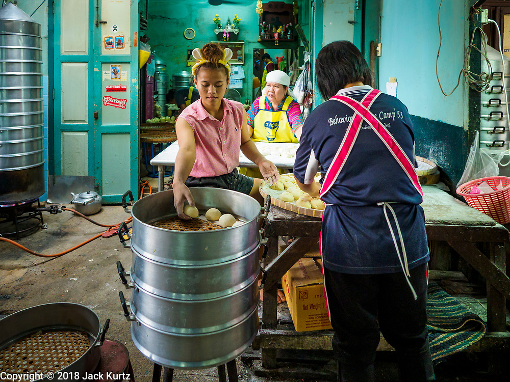 """12 FEBRUARY 2018 - BANGKOK, THAILAND: Women fill steaming racks in a home that makes steamed Chinese buns, called """"bao"""" in the Chinatown neighborhood of Bangkok. Bao are eaten at midnight on the Lunar New Year and served to guests during New Year's entertaining. Lunar New Year, also called Tet or Chinese New Year, is 16 February this year. The coming year will be the Year of the Dog. Thailand has a large Chinese community and Lunar New Year is widely celebrated in Thailand, especially in Bangkok and large cities with significant Chinese communities.    PHOTO BY JACK KURTZ"""