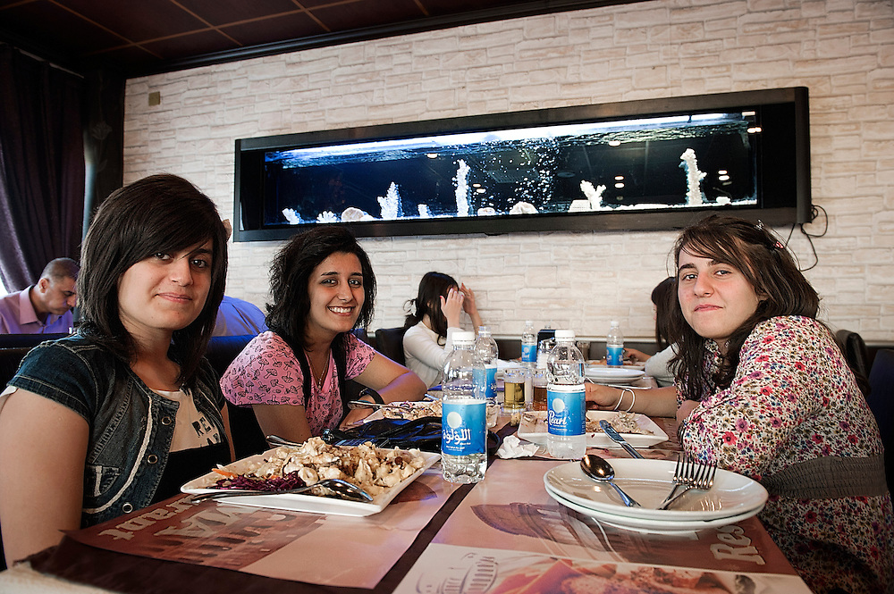 Young girls at an Italian restaurant at Sulaymaniyah, one of the main cities of Iraqi Kurdistan. Many Iraqi girls have adopted the western style in their wardrobes omitting the  veil. The economic development of Iraqi Kurdistan has permitted the people to taste and eat international cuisine, signal of prosperity and liberation.