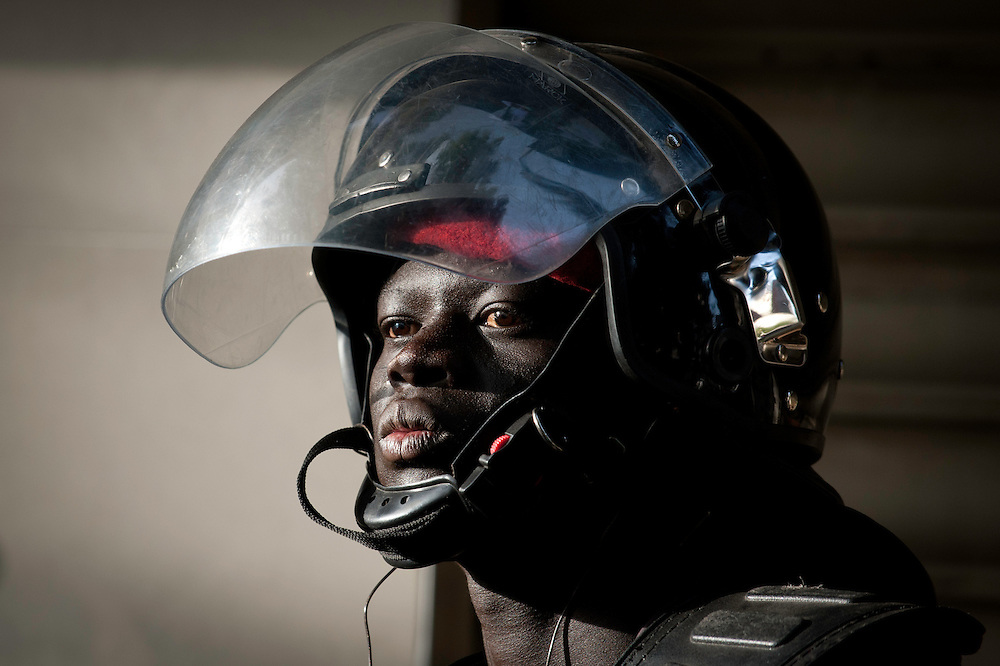 A policeman watches over a crowd during a protest in Dakar, Senegal, 21 February 2012. Violent demonstrations against incumbent President Abdoulaye Wade's re-election bid continue in the capital Dakar ahead of presidential elections. Protesters are demonstrating against a ruling by the country's top judges allowing President Abdoulaye Wade to seek a third term in office. Presidential elections are scheduled for 26 February 2012.
