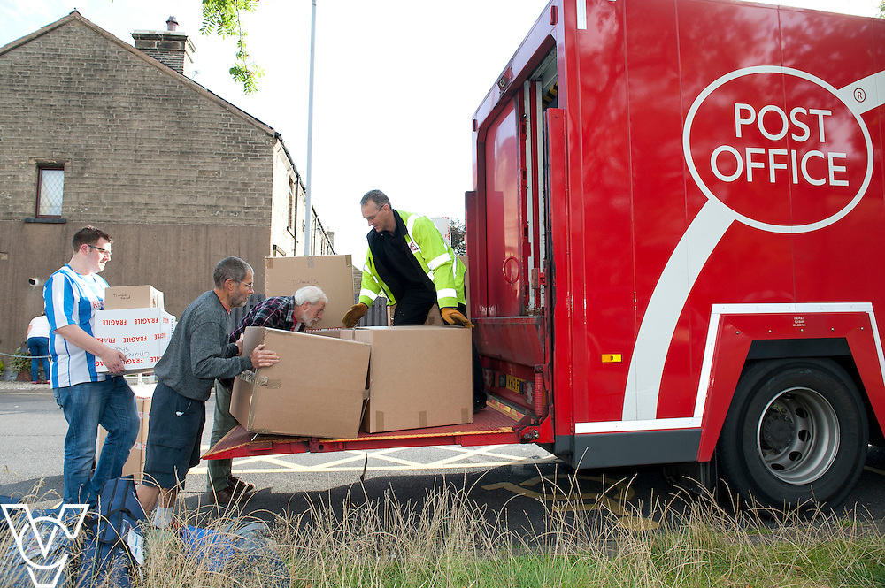 Pictured is Meltham Post Office postmaster Richard Noon, left, loading some of the boxes of donations onto the lorry<br /> <br /> A lorryload of aid is whisking its way to Syrian refugees thanks to top teamwork between a postmaster and Post Office supply chain.<br /> <br /> Meltham postmaster Richard Noon answered a local resident&rsquo;s Twitter request for a drop-off point for clothing donations. Little did he know he&rsquo;d end up with nearly 1,000 boxes!<br /> <br /> Date: September 17, 2015