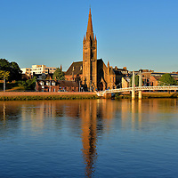 Spires Along River Ness in Inverness, Scotland<br /> At dusk, this trio of church spires creates a spectacular reflection across the River Ness.  On the left is the Old High Church. It was the site of the Parish Church in the 12th century. The tower base was created in the 15th century while the rest of the building dates to the late 18th century.  In 2003, the Old High Church merged with St Stephen's.  The Greig Street Footbridge points to the Free North Church.  Its Gothic design by Alexander Ross was finished in 1892.  On the right is St Columba's High Church. It opened in 1843 and was refurbished after a major fire in 1940.