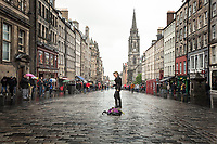 Street performer with two whips begins her act in historic district of Edinburgh, Scotland. Copyright 2019 Reid McNally.