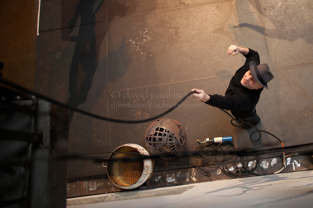 Michael Sturtz, founder of the Crucible fire arts performing arts center throws a gas line up to the second floor at the The Crucible on January 7, 2011 in Oakland, Calif.  Photograph by David Paul Morris