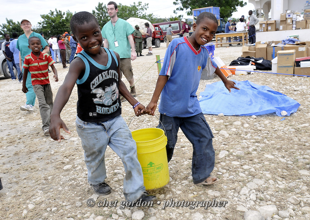 JIMANI, DOMINICAN REPUBLIC.  Dominican boys carry a bucket of water at the Jimani Health Center in Jimani, Dominican Republic on Tuesday, January 26, 2010.  © Chet Gordon/THE IMAGE WORKS