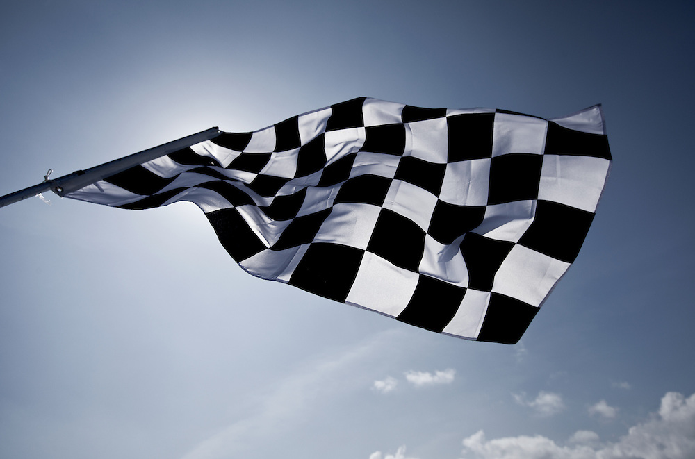 backlit image of a checkered flag against a blue sky