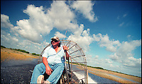 Operator on an airboat in the American Everglades going at high speed across the water on a tour.