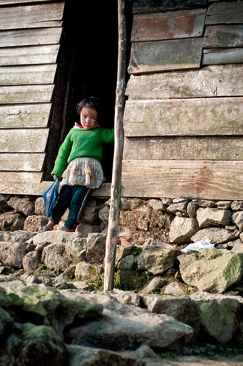 In a remote, impoverished agricultural village in India, a girl stands in the front doorway of her house before going off to school.
