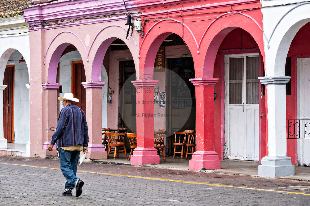 A man walks past a colorful colonnade style building in Tlacotalpan, Veracruz, Mexico. The tiny town is painted a riot of colors and features well preserved colonial Caribbean architectural style dating from the mid-16th-century.