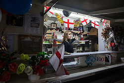 London, UK. 20 December, 2019. Cheryl Diamond points to a photograph of Syd Tothill as she prepares to close Syd's Coffee Stall for the last time. The mahogany coffee stall, part of east London's history, has been run by three generations of the same family on the corner of Shoreditch High Street and Calvert Avenue since 1919 and will go on display in the new Museum of London in Smithfield in 2024.