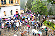 GERMANY, Fussen.  16.08.15 Many visitors, all armed with umbrellas, get ready for a tour around the Neuschwanstein Castle as it sits characteristically amongst fairy-tale like mist this afternoon. The miraculous building, built in 1886 for the eccentric Bavarian King Ludwig II, has been the inspiration for countless models, book illustrations and film sets. Rick Findler / Story Picture Agency