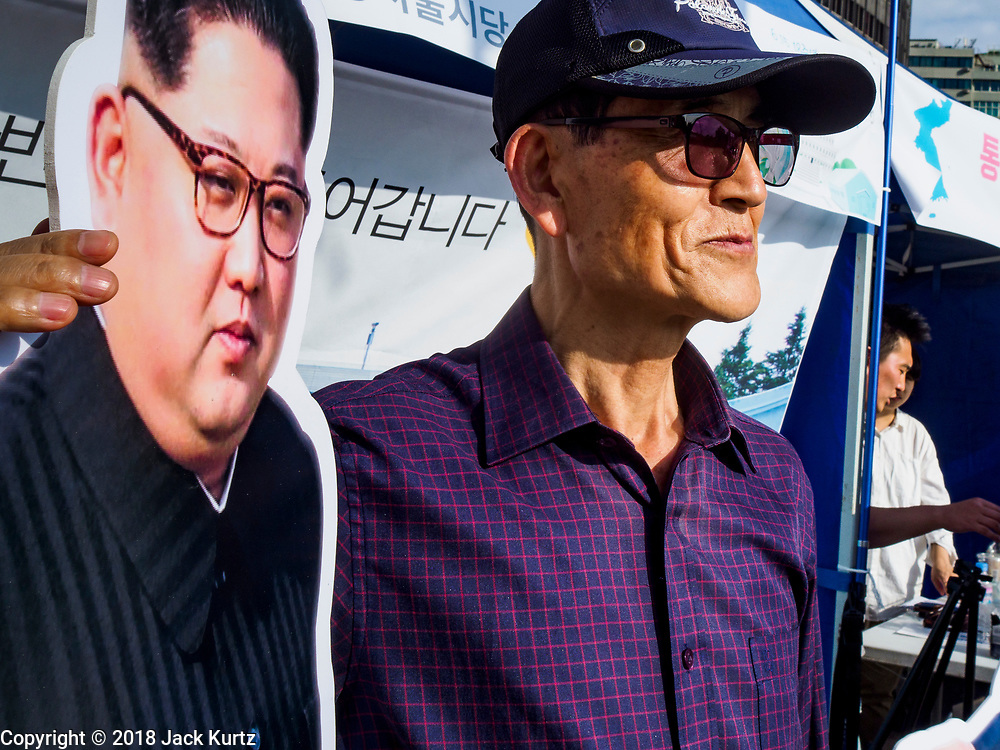 """15 JUNE 2018 - SEOUL, SOUTH KOREA: A man poses for a photo with a cutout of North Korean leader Kim Jong-un during a rally to mark the anniversary of the signing of the June 15th North–South Joint Declaration between South Korea and North Korea. The Declaration was negotiated by late South Korean President Kim Dae-jung and North Korean leader Kim Jong-il and signed on 15 June 2000. It was a part of South Korea's """"Sunshine Policy,"""" which guides the South's relationship with North Korea. This year's observance of the anniversary was bolstered by the recent thawing in relations between North Korea and South Korea and the US.     PHOTO BY JACK KURTZ"""