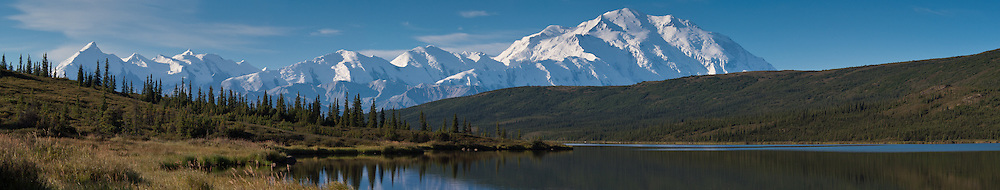 Sun rises on Denali and the Alaska Range as seen from Wonder Lake in Denali National Park and Preserve in Alaska. Denali is North America's tallest peak at 20,310 feet and towers over 18,000 feet above the surrounding lowlands. Other mountain peaks pictured include: Mount Brooks, Mount Silverthrone, Mount Tatum, and Mount Carpe. SPECIAL NOTE: This image is a panorama composite consisting of multiple overlapping images stitched together.