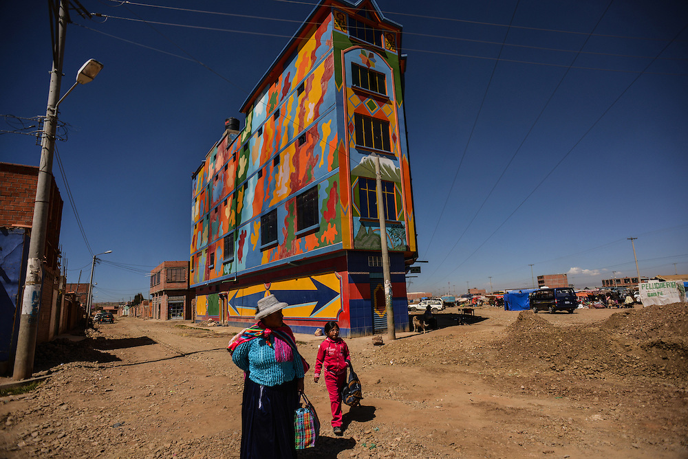 """The outward sign of the changes in El Alto are the brightly colored buildings, often topped with luxury chalets, that its newly prosperous merchant class began to build over the last two years..Residents recall this building as being the first of it's kind, universally known as, """"the clown house"""", it stands on a stretch of highway that is rapidly filling in with homes and businesses. There are many others. Some have diamonds painted on them or created in bas relief in the stucco facade - an unmistakable sign of wealth. But the color is what is most striking.  Photo by Meridith Kohut for The New York Times"""