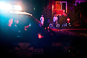 Onlookers are illuminated by a police car as it drives away from the scene of a shooting on Dupont Street and Josephine Street in Flint. One male victim was taken to the hospital for a gunshot wound to the abdomen and was in serious condition.