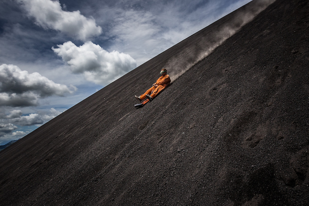 LEON, NICARAGUA - SEPTEMBER 18, 2014:  A tourist volcano boarding down Cerro Negro volcano. Boarders can reach speeds of up to 95 kilometers per hour. Guided tours are available from $29 USD to board down the volcano, located an hour outside of Leon. PHOTO: Meridith Kohut