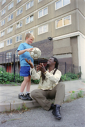 Boy and carer playing with football outside block of flats,
