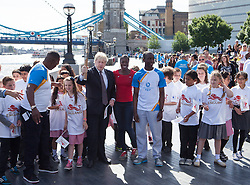 Image ©Licensed to i-Images Picture Agency. 06/06/2014. London, United Kingdom. Mayor of London Boris Johnson holds the Commonwealth Games Queen\'s Baton Relay with local schoolchildren and Commonwealth champion Christine Ohuruogu MBE (centre)  Faramolu Johnson (right) and Michael Pusey (talking with children) to the capital as part of the England led of a journey that will see it travel 190,000 kilometres over 288 days. City Hall, The Queen\'s Walk. Picture by Daniel Leal-Olivas / i-Images