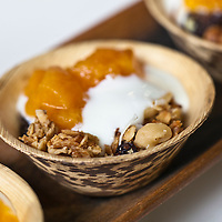 Small bowls of granola with apricot jam and fresh yogurt.