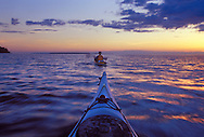 A pair of sea kayakers paddle from Otter to York Island at dusk in Apostle Islands National Lakeshore near Bayfield, Wis.