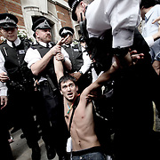 A protester is detained by police during a demonstration about Public Sector pension cuts