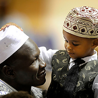 Three-year-old Zahir Bashir plays with the hat of his dad, Elyas, during prayers marking Ramadan, a holy month for Muslims. A celebration was held at the Ramkota Exhibit Hall in Sioux Falls. Ramadan observances include fasting from sunrise to sunset.