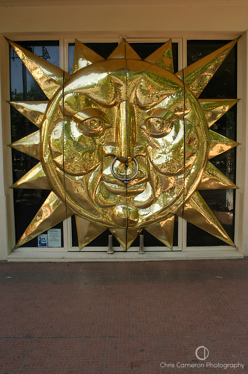 Shop doorway in the shape of a sun with a nosering as handles, Valencia, Spain. 22/6/2005