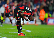AFC Bournemouth forward Benik Afobe leans forward and crosses himself after scoring his opening goal for Bournemouth during the Barclays Premier League match between Bournemouth and Norwich City at the Goldsands Stadium, Bournemouth, England on 16 January 2016. Photo by Graham Hunt.